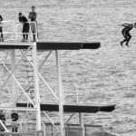 Black and white of students jumping off of a high dive into the sea