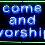"""A neon sign which reads """"Come and worship"""""""