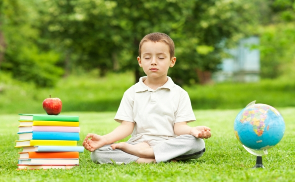 Child in lotus position meditating between textbooks and globe